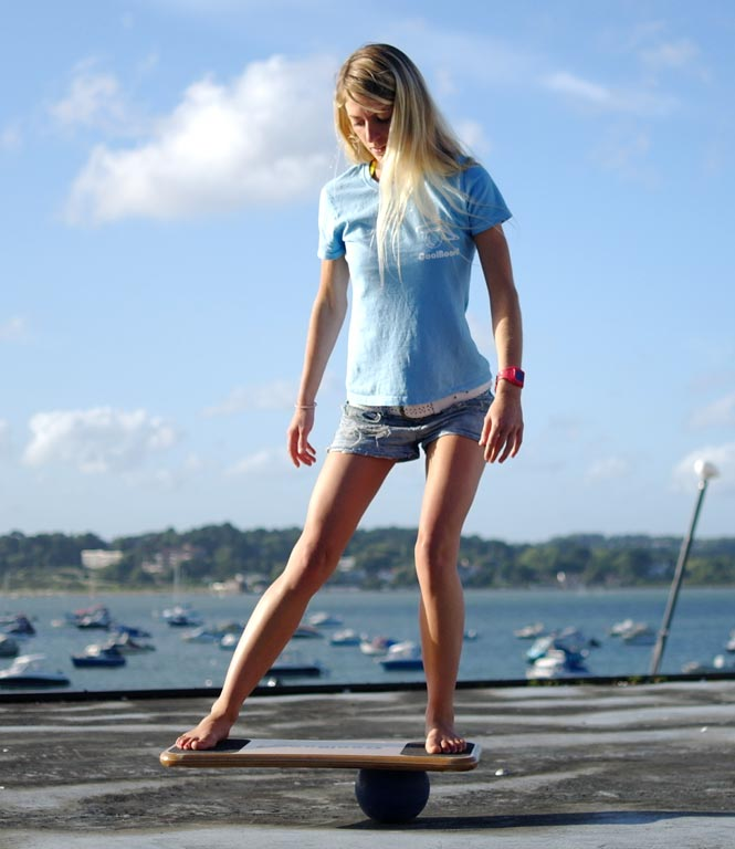 Woman standing on CoolBoard doing Balance Exercise for Core Strength, sea and boats in background