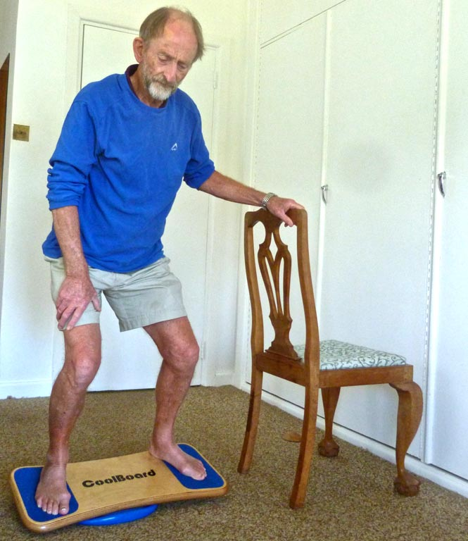 Peter Smith, 75, on his CoolBoard Wobble Board. He is doing balance exercise for elderly on the Easy Start Balance Disc using a chair for support.