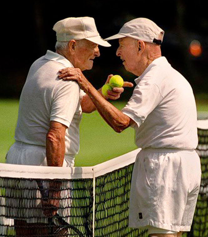 two senior tennis players meeting at the net for a lively discussion