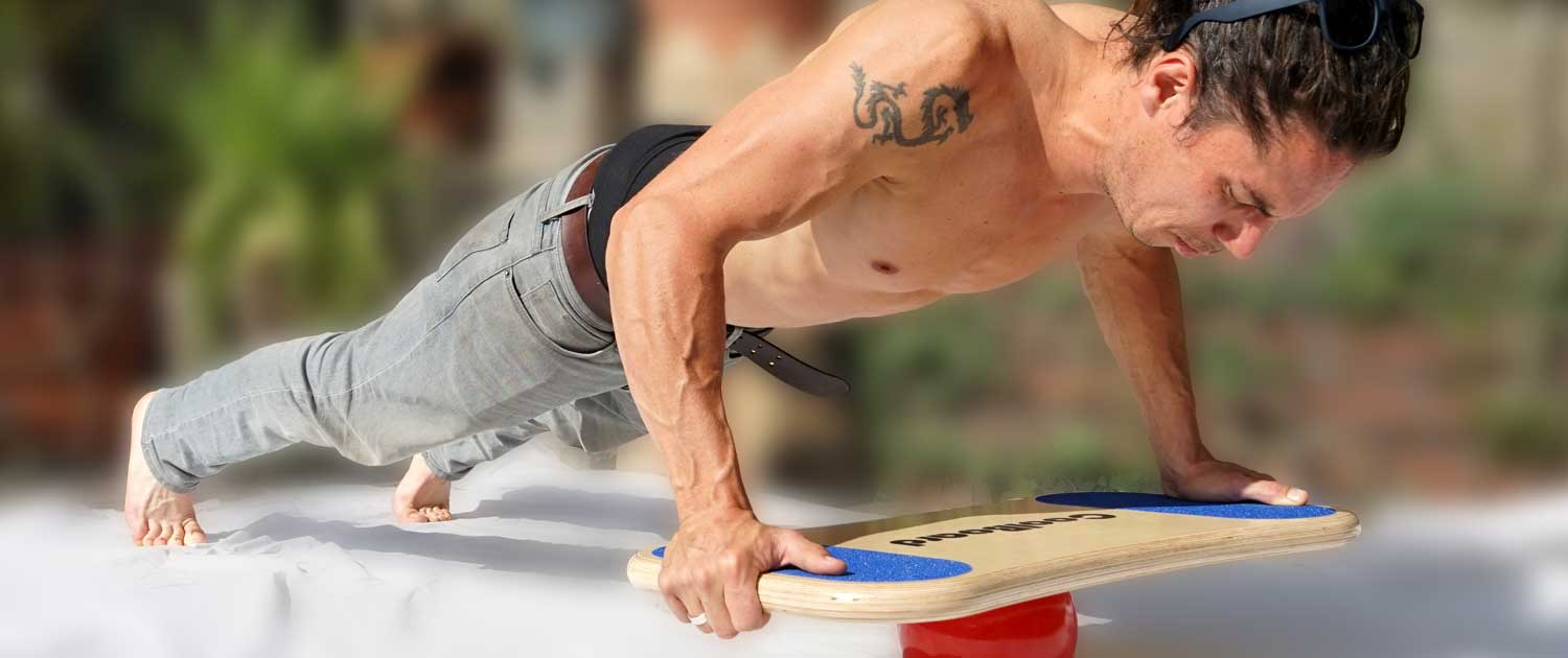 Man with ripped muscles doing Core Busting Core Exercise CoolBoard Push-up with background