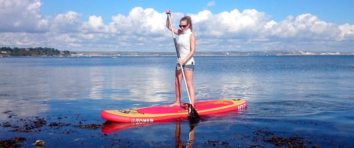 Lady on her Stand Up Paddle Board using her balance training to balance on her SUP on the sea
