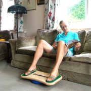 elderly lady using CoolBoard wobble board sat on a sofa while reading a magazine